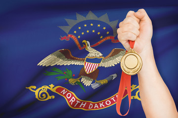 Medal in hand with flag on background - State of North Dakota.