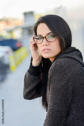 Young woman with green eyes and eyeglasses in urban background