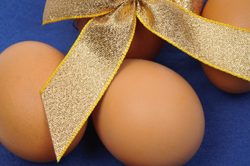 Close-up of brown Easter eggs with gold ribbon