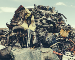 A heap of twisted metal, a scrap metal yard, a collection of objects for recycling.