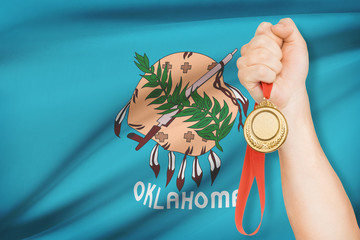 Medal in hand with flag on background - State of Oklahoma.