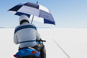 A motorcyclist sheltering under an umbrella, on the start line at Speed Week, on the Bonneville Salt Flats.