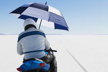 A motorcyclist sheltering under an umbrella, on the start line at Speed Week, on the Bonneville Salt Flats.
