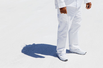 A man in white overalls, a race official timekeeper at a car racing event,  at Speed Week on Bonneville Salt Flats.