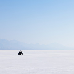 Motorcyclist riding on the flat white surface of the salt pan on the Bonneville Salt Flats.