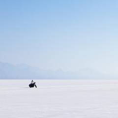 Motorcyclist riding on the flat white surface of the salt pan on the Bonneville Salt Flats.