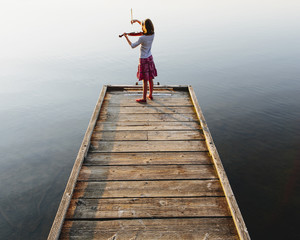A ten year old girl playing the violin at dawn on a wooden dock.