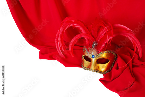 Venetian mask with red feathers on red fabric