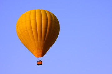 Yellow hot air balloon in blue sky