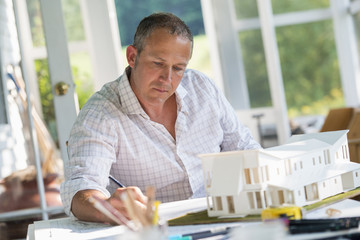 A farmhouse kitchen. A model of a house on the table. Designing a house. A man using a pencil drawing on a plan.