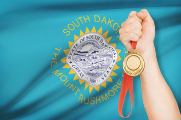 Medal in hand with flag on background - State of South Dakota.