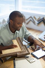 A young man at his workbench in a picture framing studio. Surrounded by samples. Using a digital tablet.