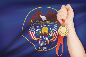 Medal in hand with flag on background - State of Utah.