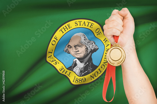 Medal in hand with flag on background - State of Washington.