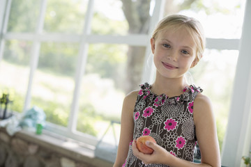 A young girl in a floral dress holding a peach fruit.
