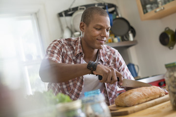 A man in a kitchen slicing a loaf of bread.