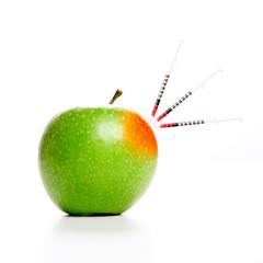 A syringe on a GMO, trangenic, apple.