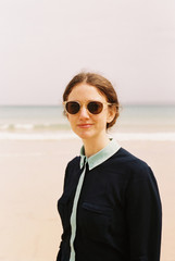 A woman wearing sunglasses on a beach.
