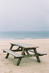 A wooden picnic bench on the sand. View out to sea.