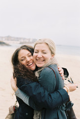 Two women cheek to cheek hugging on a beach.