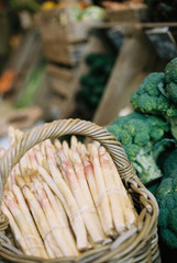 Bundles of white asparagus and broccoli florets on a vegetable stall.