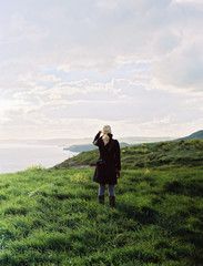 A woman looking along the coastline, inlets and cliffs.