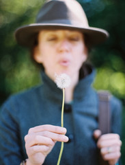 A woman blowing a dandelion clock seedhead. A traditional game.