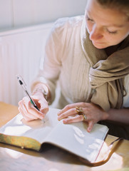 A woman using a coloured pen drawing on a blank page of a diary.