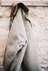 A traditional warm jacket with corduroy collar hanging from a pen on a stone wall.
