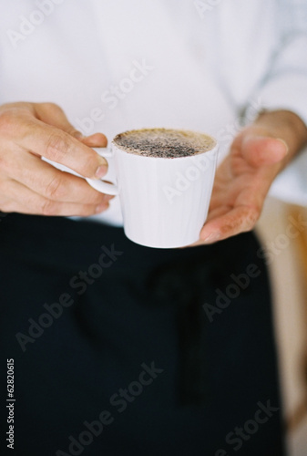 A person holding a full cup of coffee. Froth.