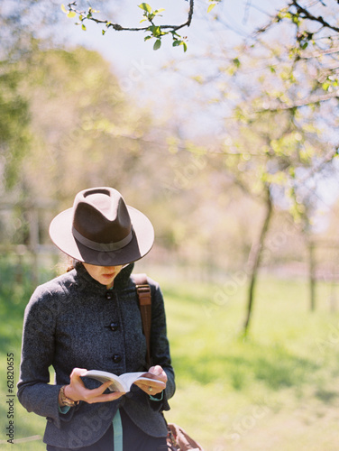 A woman in a hat, reading a book.