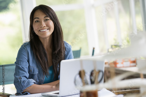 A woman in an office, working at a laptop computer.
