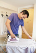 A man ironing a shirt on the ironing board.