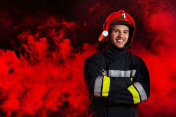 Firefighter in red helmet posing with arms crossed.