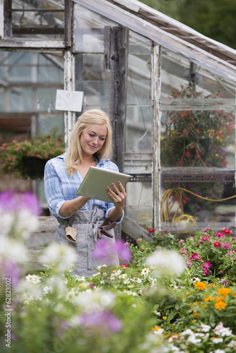 An organic flower plant nursery. A woman working, using a digital tablet.