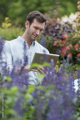 An organic flower plant nursery. A man working, using a digital tablet.