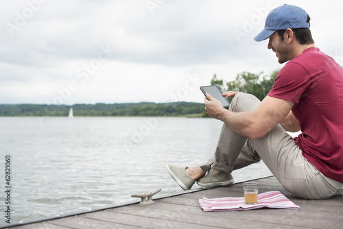A man seated on a jetty by a lake, using a digital tablet.
