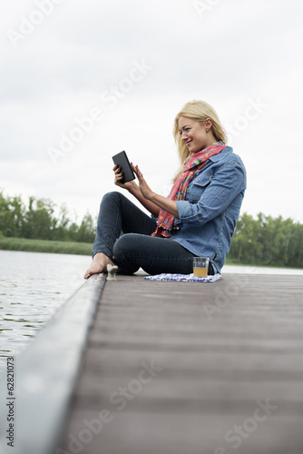 A woman sitting on a jetty by a lake, using a digital tablet.