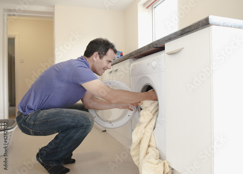 A man putting the laundry into the washing machine.