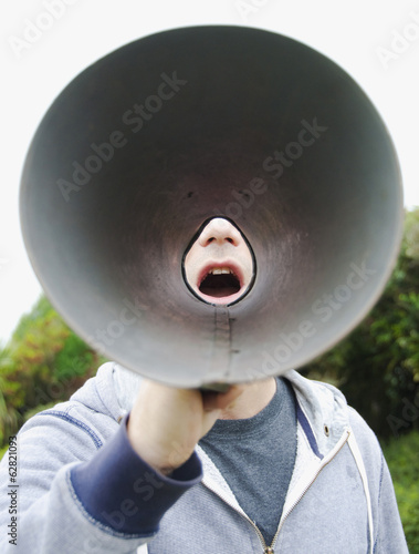 A man using a megaphone in the open air.