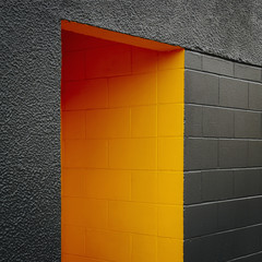 A doorway recess, painted orange in a grey block concrete wall.
