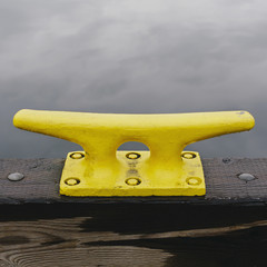 A large yellow mooring cleat on the wharf side in Seattle.