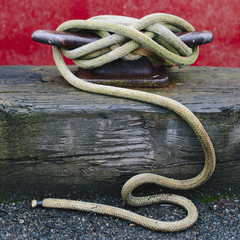 Close up of a wharfside mooring cleat with a fishing boat rope tied around it.