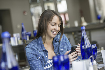 A woman seated in a cafe using a smart phone.