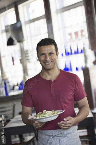 A cafe interior. A man in a waiter's apron serving a meal.