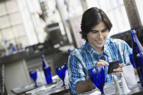 A man seated in a cafe using a smart phone.