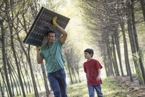 A man carrying a solar panel down an avenue of trees, accompanied by a child.