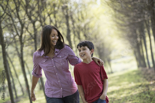 A woman and a child walking down an avenue of trees.