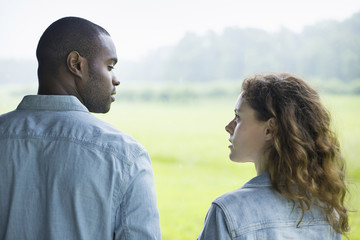 A young man and woman, a couple standing side by side. Looking at each other.