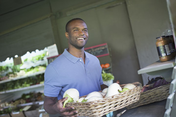 An organic fruit and vegetable farm. A man sorting vegetables.